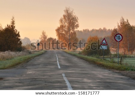 Country road and roadsigns in autumn - stock photo
