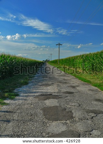 Country Road between Corn Fields - stock photo