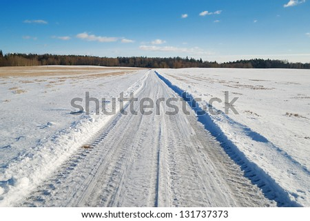 Country road covered in snow in a field - stock photo