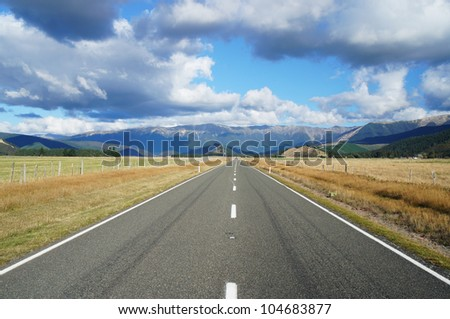 Country Road Going To Mountains on Sunny Day - New Zealand - stock photo