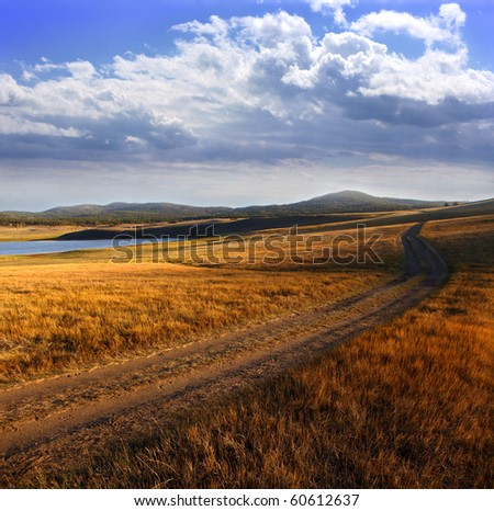 Country road in autumn day. - stock photo