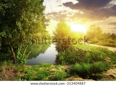 Country road near river in sunny evening - stock photo