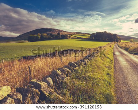 Country Road Or Lane And Dry Stone Wall Through Scottish Rural Lanscape At Dusk - stock photo
