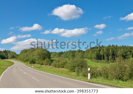 Country road through flat region with woods and meadows; Overland journey on a sunny summer day; Mystery tour - stock photo