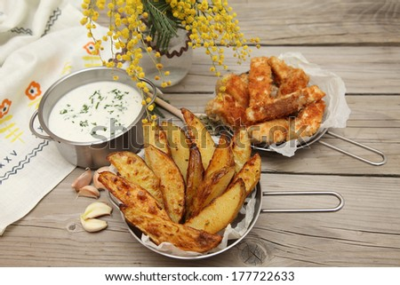 Country style potatoes. Potato wedges with slices of fried fish with rosemary, garlic and beer on a wooden background. Food style. - stock photo