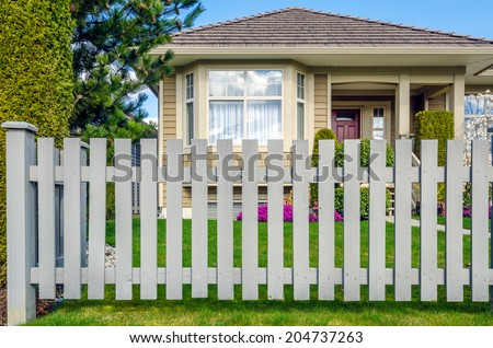 Country style wooden fence with a beautiful house behind. Exterior design. - stock photo