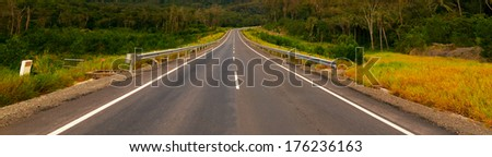 Countryside asphalt road surrounded by nature - stock photo