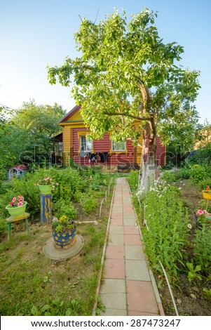 Countryside cottage in Russia with blooming garden around - stock photo