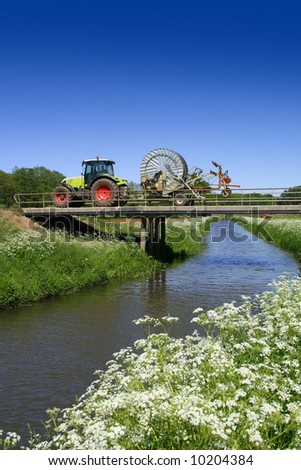 Countryside. Farmer driving his tractor over a bridge over a natural stream with verge of beautiful white flowers. - stock photo