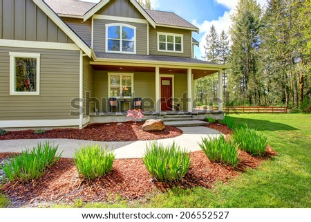 Countryside house exterior. View of entrance column porch with stairs and walkway - stock photo