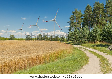 Countryside landscape with a field of ripening rye and wind electric-turbines.  Conceptual image illustrating sustainable agriculture and alternative production of electric energy - stock photo