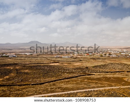 Countryside landscape with desert hills and village in light haze under cloudy sky. - stock photo