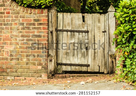 Countryside scene. Rustic old wooden gate in brick wall. - stock photo