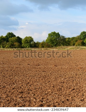 Countryside View of Bare Earth of a Plowed Farmland Field in Rural England  - stock photo