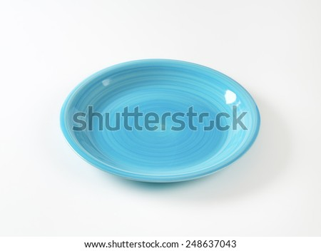 Coup shaped ceramic plate with a blue color glaze - stock photo