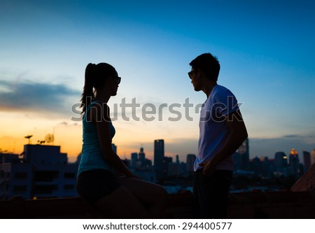 Coupe enjoying the city view from a roof top. - stock photo