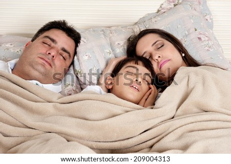 Couple and a child in the bed . - stock photo