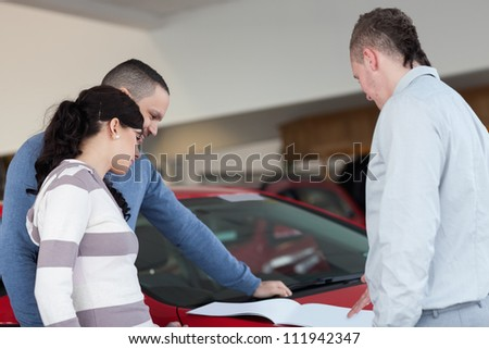 Couple and a salesman looking at a document in a car shop - stock photo