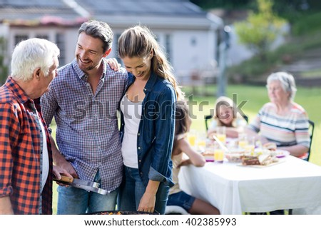 Couple and a senior man at barbecue grill preparing a barbecue in garden - stock photo