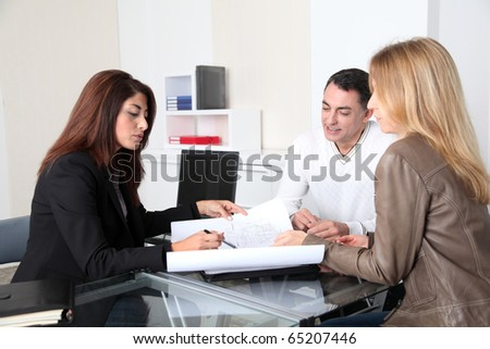 Couple and architect looking at plan - stock photo