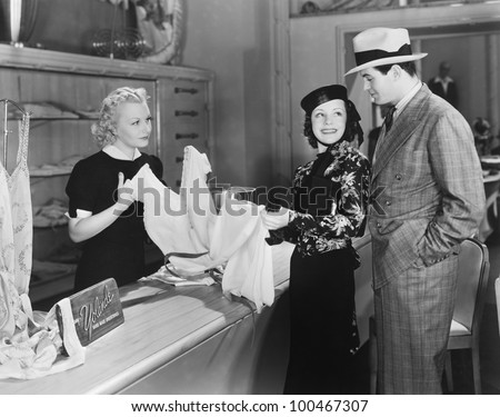 Couple and clerk in shop - stock photo