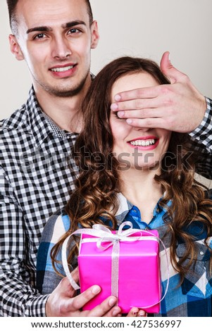 Couple and holiday concept. Smiling young man surprising cheerful woman with gift box covering her eyes with hand - stock photo