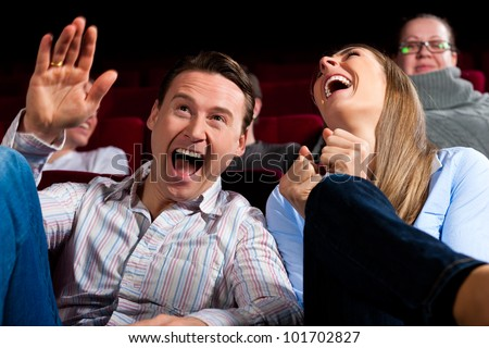 Couple and other people, probably friends, in cinema watching a movie, it seems to be a funny movie - stock photo