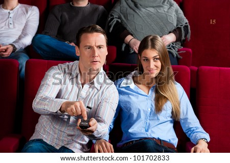 Couple and other people, probably friends, in cinema watching a movie, they try to switch to another program that is not possible in a cinema - stock photo