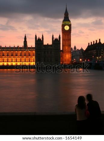 Couple at Big Ben after sunset - stock photo