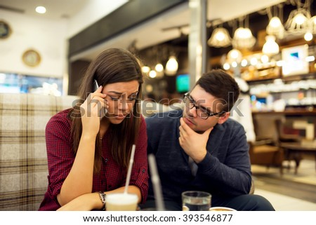Couple at cafe, she is talking on mobile phone hearing bad news while he is consoling her. - stock photo