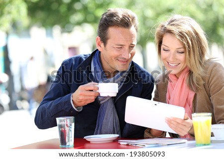 Couple at coffee shop websurfing with tablet - stock photo