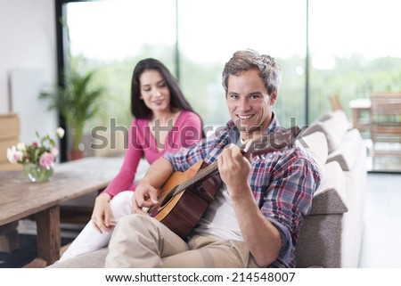 couple at home man at foreground playing guitar - stock photo