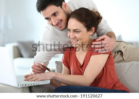 Couple at home shopping online with laptop - stock photo