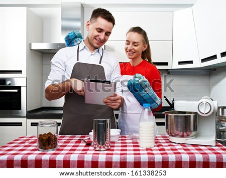 Couple at kitchen cooking together with tablet pc - stock photo