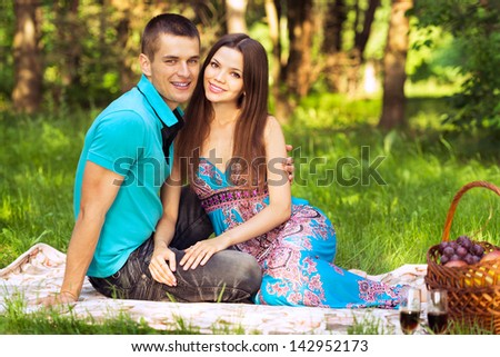 couple at outdoor picnic in forest park - stock photo