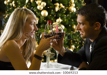 Couple at restaurant on dinner party. They're looking at each other and raise a toast. - stock photo