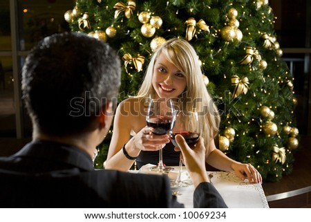 Couple at restaurant on dinner party. They're looking at each other and raise a toast. Focused on her. - stock photo
