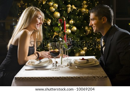 Couple at restaurant on dinner party. They're looking at each other and smiling. - stock photo