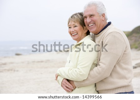 Couple at the beach embracing and smiling - stock photo