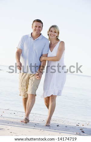 Couple at the beach holding hands and smiling - stock photo