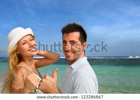 Couple at the beach showing thumb up - stock photo