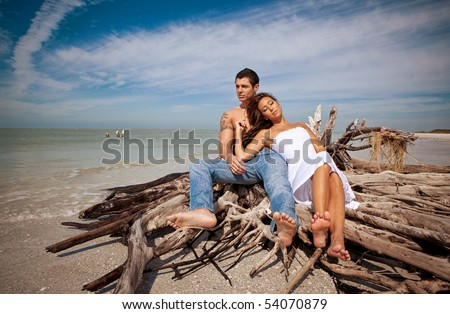 Couple at the beach, sitting on wood, relaxing - stock photo