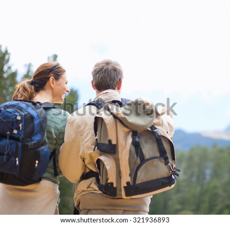 Couple Backpackers hiking on the path in mountains - stock photo