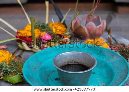 Couple Balinese colored flowers dropped on stones with turquoise dishes, religious offerings in Bali. Indonesia. Selective focus. - stock photo