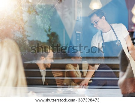 Couple being served by a waiter in busy cafe - stock photo
