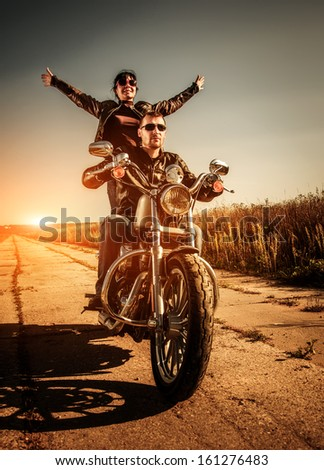 Couple Bikers in a leather jacket riding a motorcycle on the road - stock photo