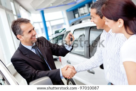 Couple buying a car and salesman handling keys - stock photo