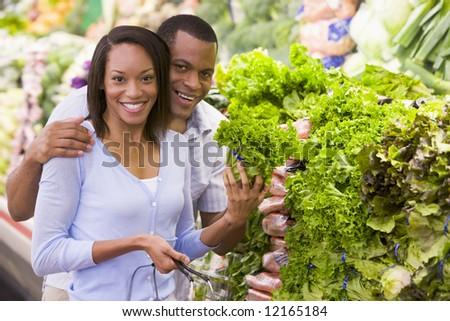 Couple buying fresh produce in supermarket - stock photo
