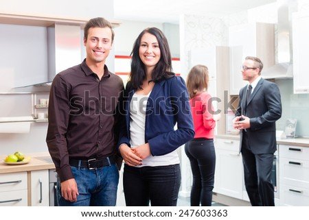 Couple buying in kitchen in store showroom - stock photo