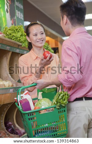 Couple buying vegetables in supermarket, Beijing - stock photo